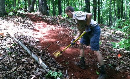 Graham Haynie, a boy scout with Charlottesville's Troop 37, clears a new trail with a McCleod for the Saunders-Monticello trail system on Carter Mountain May 25. The project was done in collaboration with the Charlottesville Area Mountain Bike Club.