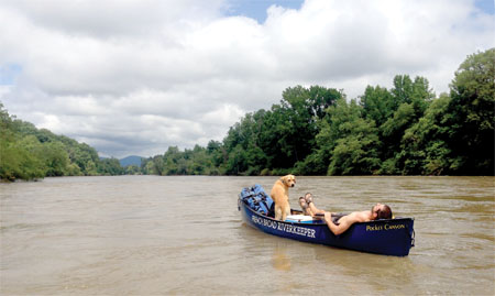 Hartwell Carson and June Bug testing the buoyancy of their canoe on the French Broad River Trail.