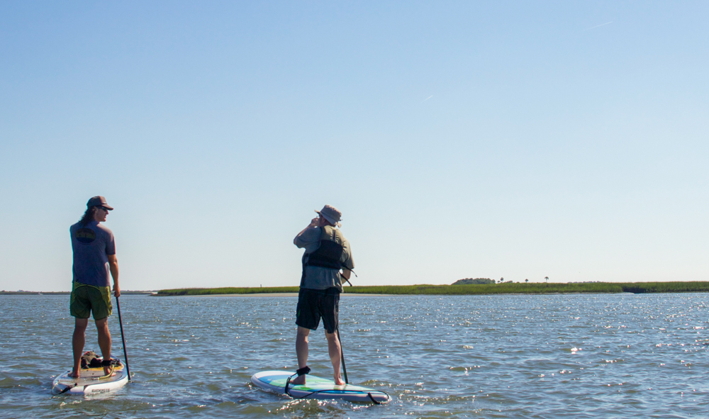 Jon (left) showing Bob (right) the basics of stand up paddleboarding.