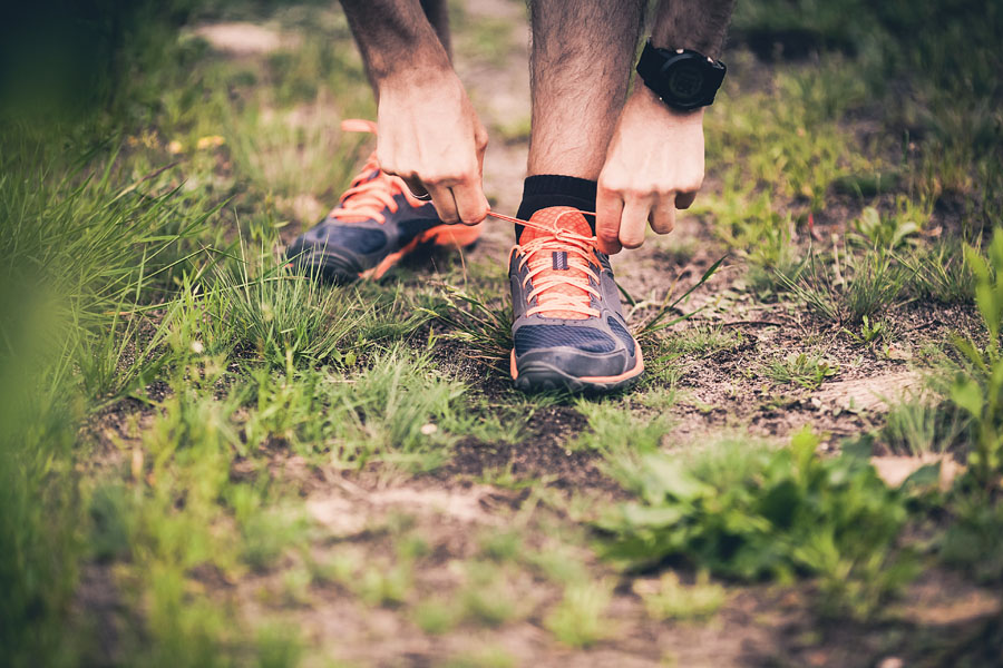 Runner tying sports shoe on trail
