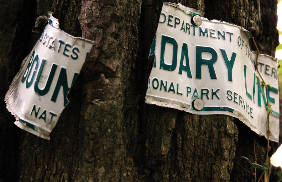 A Department of the Interior Boundary sign ripped from tree growth