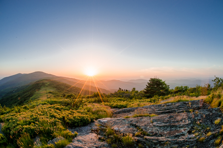 Sun rays fan out as the sun crests the ridge behind Roan Mountain