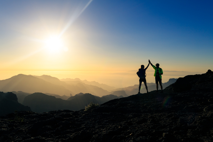 Couple hikers celebrating success in sunset mountains, accomplish with arms up outstretched. Young man and woman on rocky mountain range looking at beautiful inspirational landscape view, Gran Canaria Canary Islands.