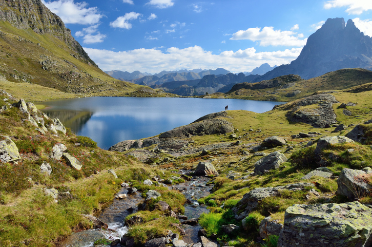 A mountain stream runs to the alpine lake Gentau. There are tourists and the recognizable summit Pic du Midi d'Ossau in the background.