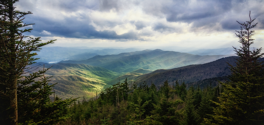 A wide view of sunlit valleys below Clingmans Dome - the highest point in the Great Smoky Mountains National Park. Picturesque mountain landscape background with copy space.