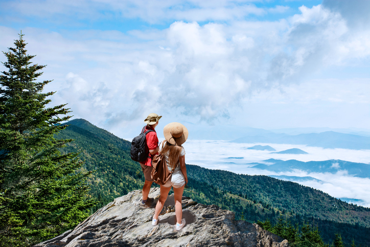 Couple on hiking trip, standing on top of the mountain over the clouds, looking at beautiful summer mountain landscape. People enjoying beautiful view. Close to Asheville, North Carolina, USA.