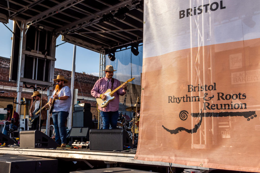 Wide shot of the band 49 Winchester performing on stage with a Bristol Rhythm and Roots Reunion banner in the foreground. Three men hold guitars while wearing cowboy hats while a woman sits at an instrument with a cowboy hat on as well.