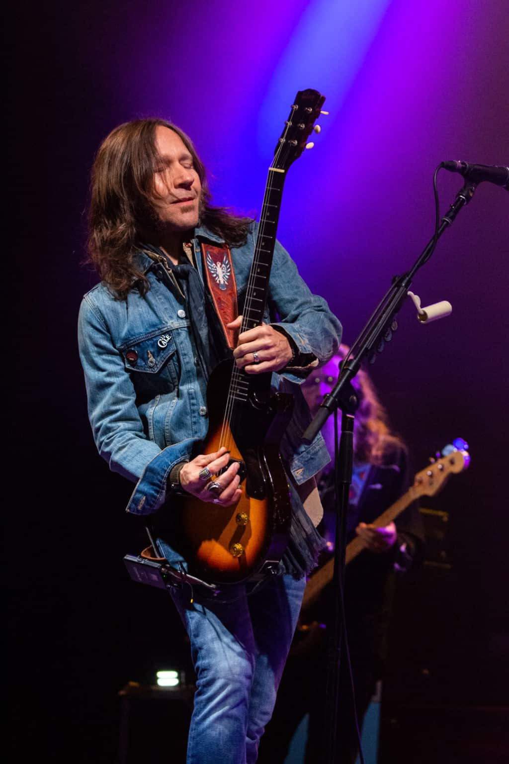 Medium shot of Blackberry Smoke smiling with eyes closed while playing an electric guitar with purple lights shining in the background