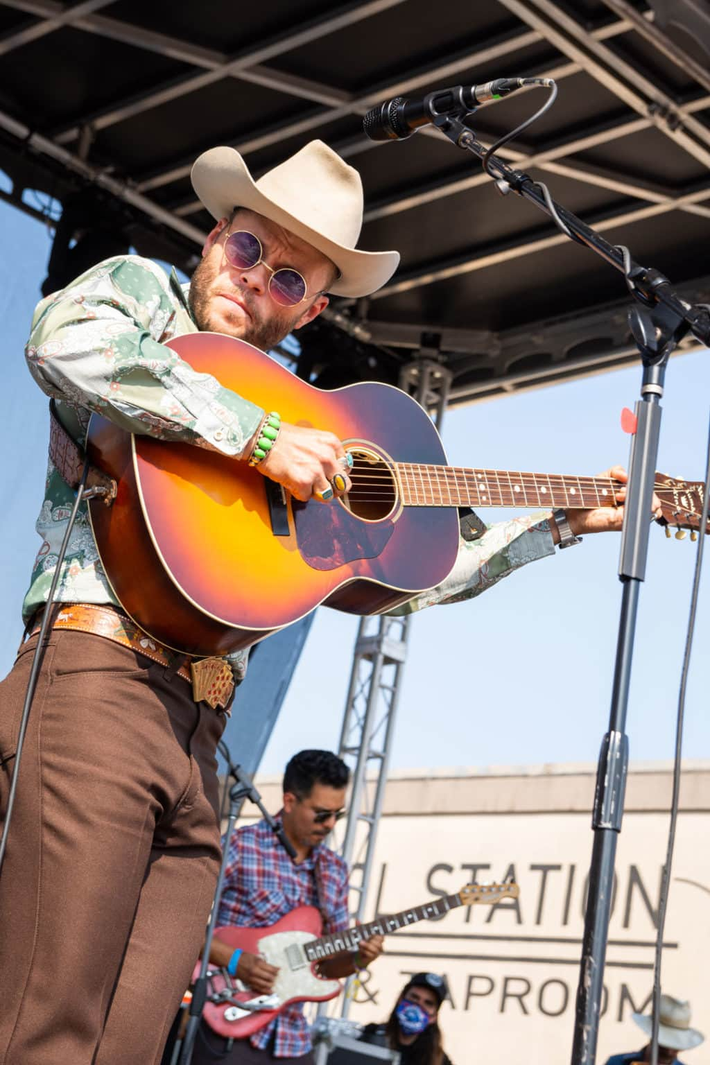 Medium shot of Charlie Crockett holding his acoustic guitar high up as he picks it. He is wearing a cowboy hat, round sunglasses, colorful jewelry, and a belt with white horses on it and a card hand belt buckle.