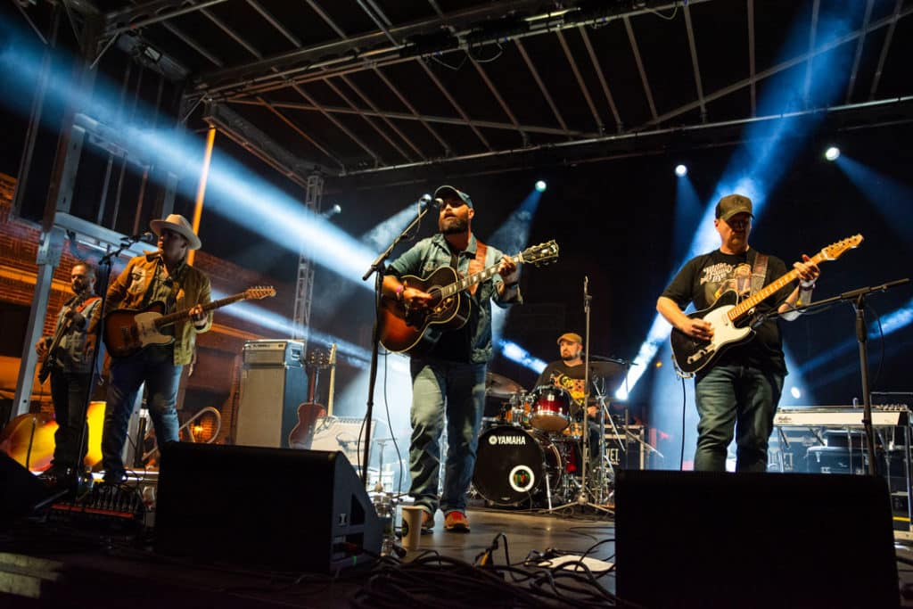 Wide shot of Folk Soul Revival playing on stage at night with beams of blue light shining in multiple directions. Four men can be seen standing and holding guitars with a dummer playing at the back of the stage.
