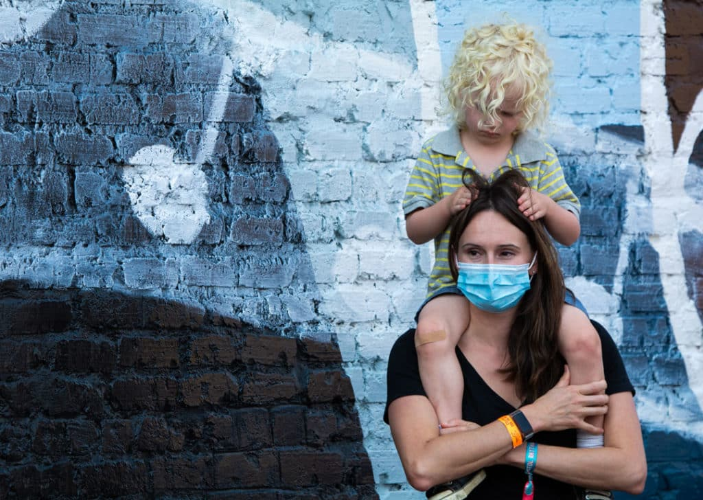 A woman smiles under her medical mask while standing in front of a mural while a child sits on her shoulders and pulls at her hair. The woman is wearing a festival pass bracelet.