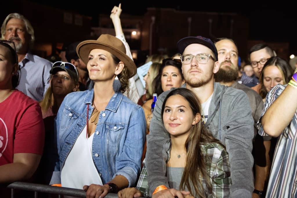 A couple stands and smiles in a crowd of fans enjoying the show at night.