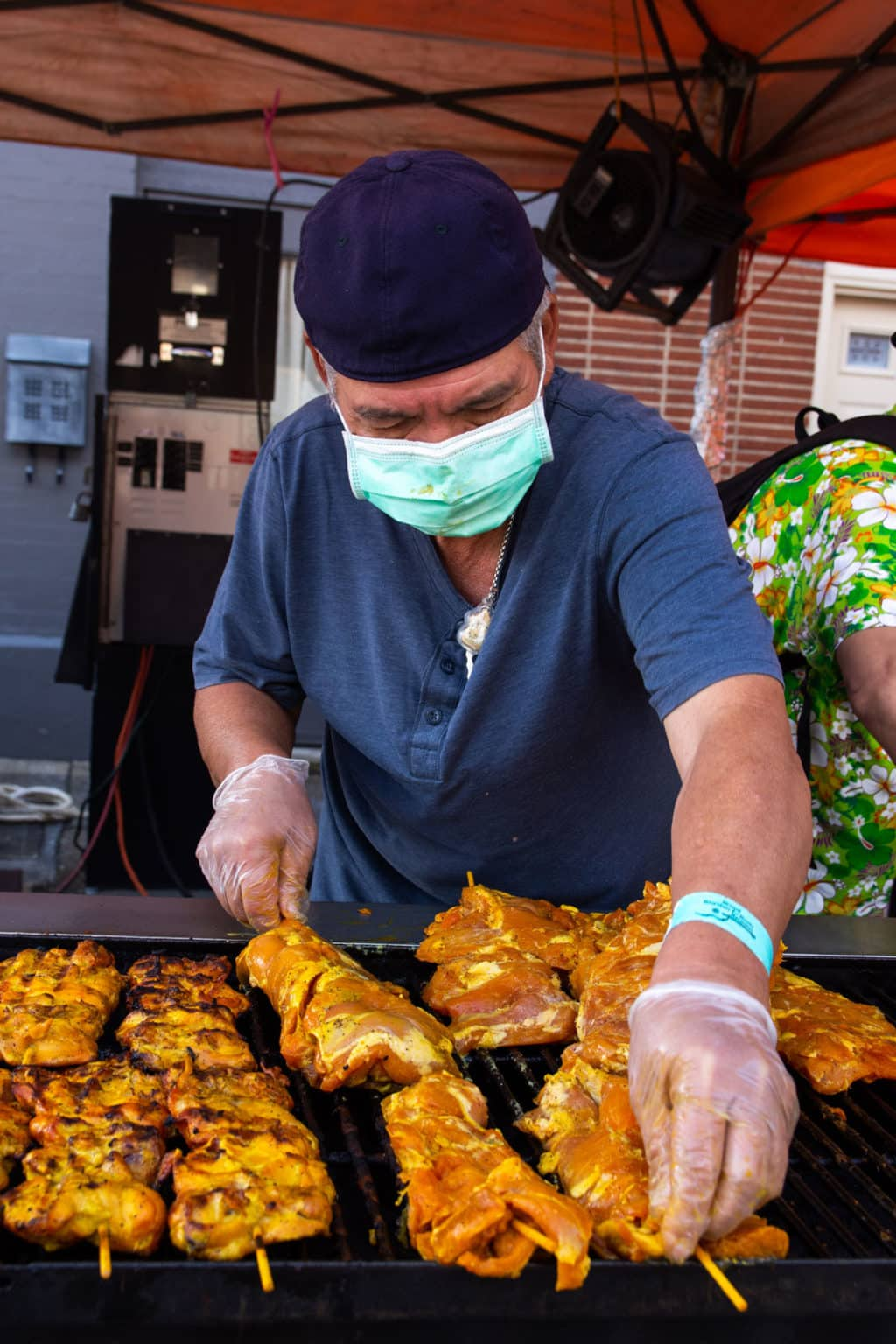 A vendor cooks meat on a grill while wearing a backwards hat and a medical mask.